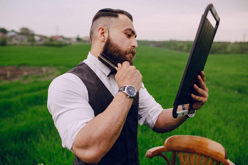 Bearded men using his beard brush